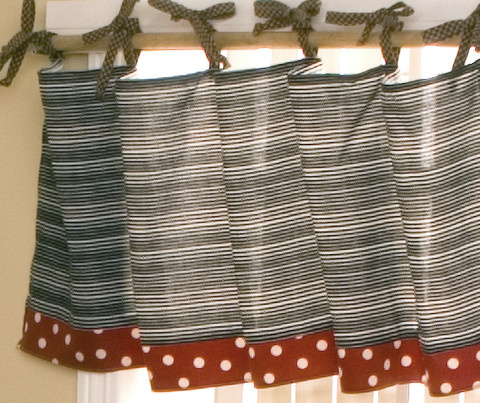 "Part of the Pirate's Cove crib bedding sets collection is this 100% cotton curtain valance of black, gray and white stripes, trimmed in red polka-dots ties to a rod with brown checker cording.  Decorate your baby boy nursery with this beautiful piece of boy nursery decor!  Measurements: 55"" x 16""."